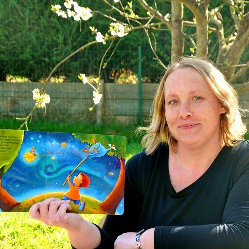 Femme assise qui tient un livre ouvert pour enfant