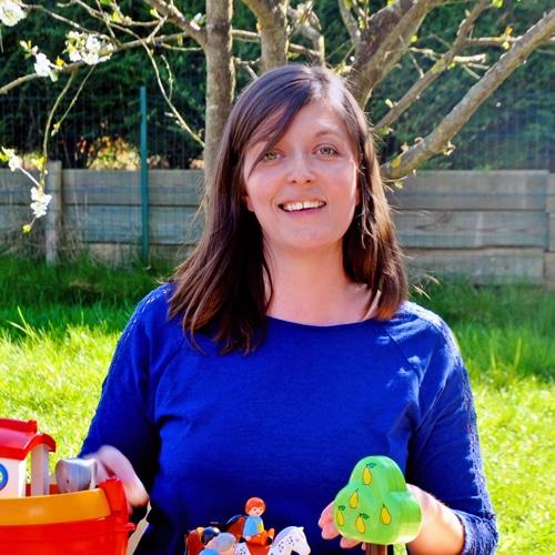 Femme assise qui sourit avec des jouets pour enfant devant elle