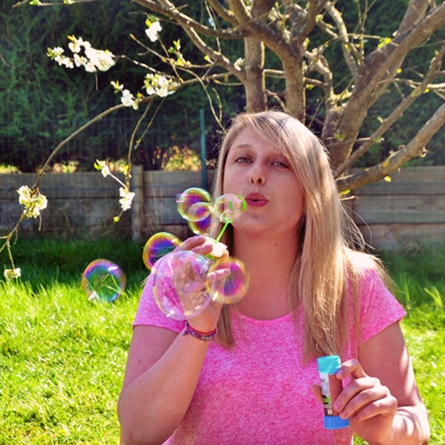 Femme avec un t-shirt rose qui fait des bulles de savon