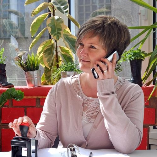 Femme à son bureau qui téléphone et qui tient un tampon encreur
