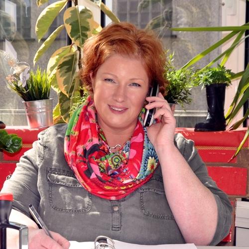 Femme assise à son bureau qui téléphone en notant quelque chose