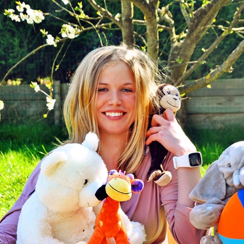 Femme aux cheveux blonds entourée de peluches