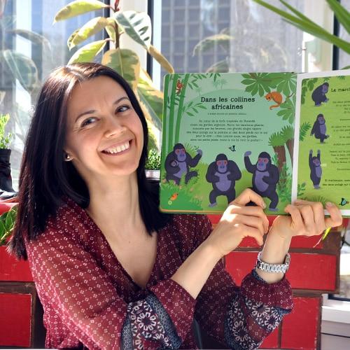 Femme souriante tenant une livre pour enfant