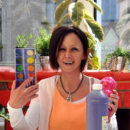 Une femme qui sourit tient un tube de couleur et une palette de couleurs pour enfant