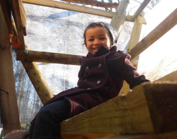 Enfant qui sourit dans une cabane en bois