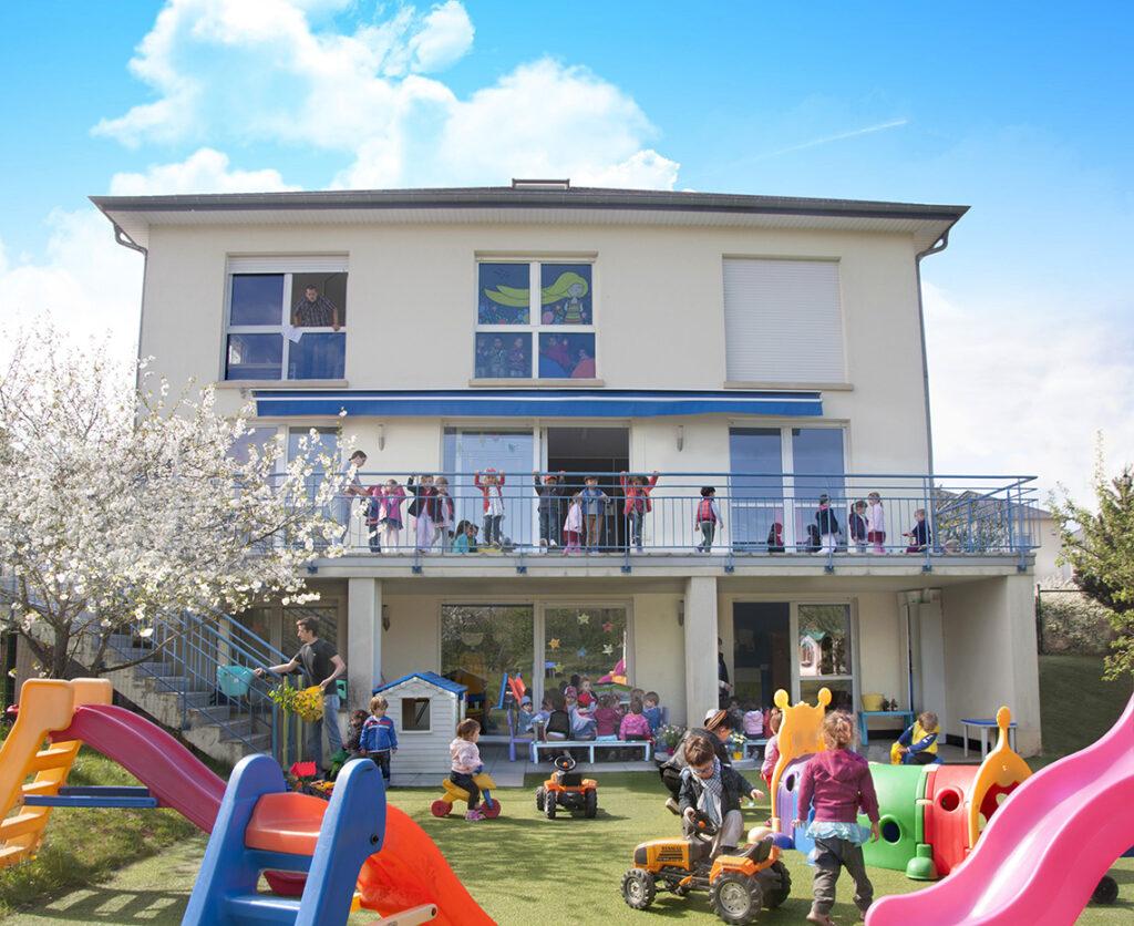 Jardin et façade arrière de la crèche Les P'tits Malins de Strassen avec des enfants qui jouent