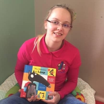 Une éducatrice de la crèche les p'tits malins avec un livre pour enfant