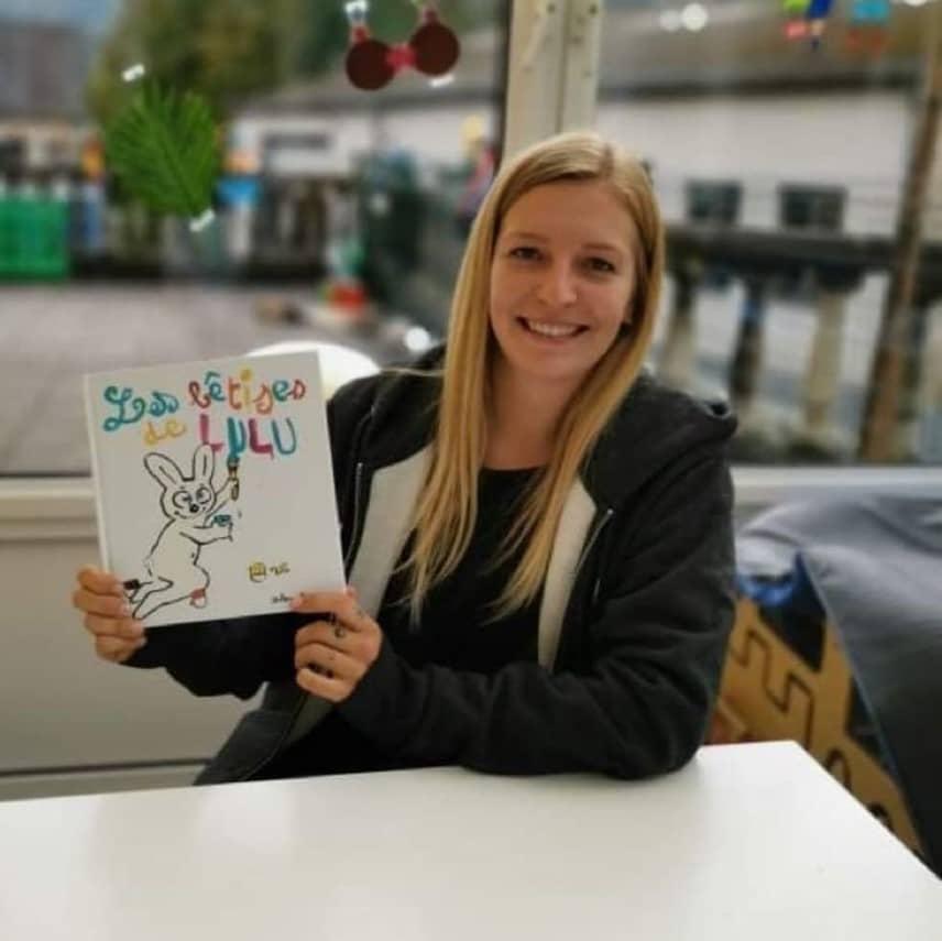 Une jeune femme assise tenant un livre pour enfant