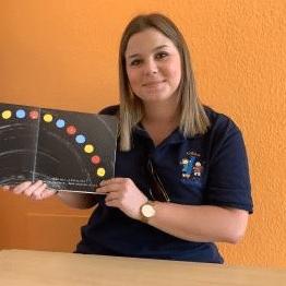 Une éducatrice de la crèche les p'tits malins d'Erpeldange avec un livre pour enfant