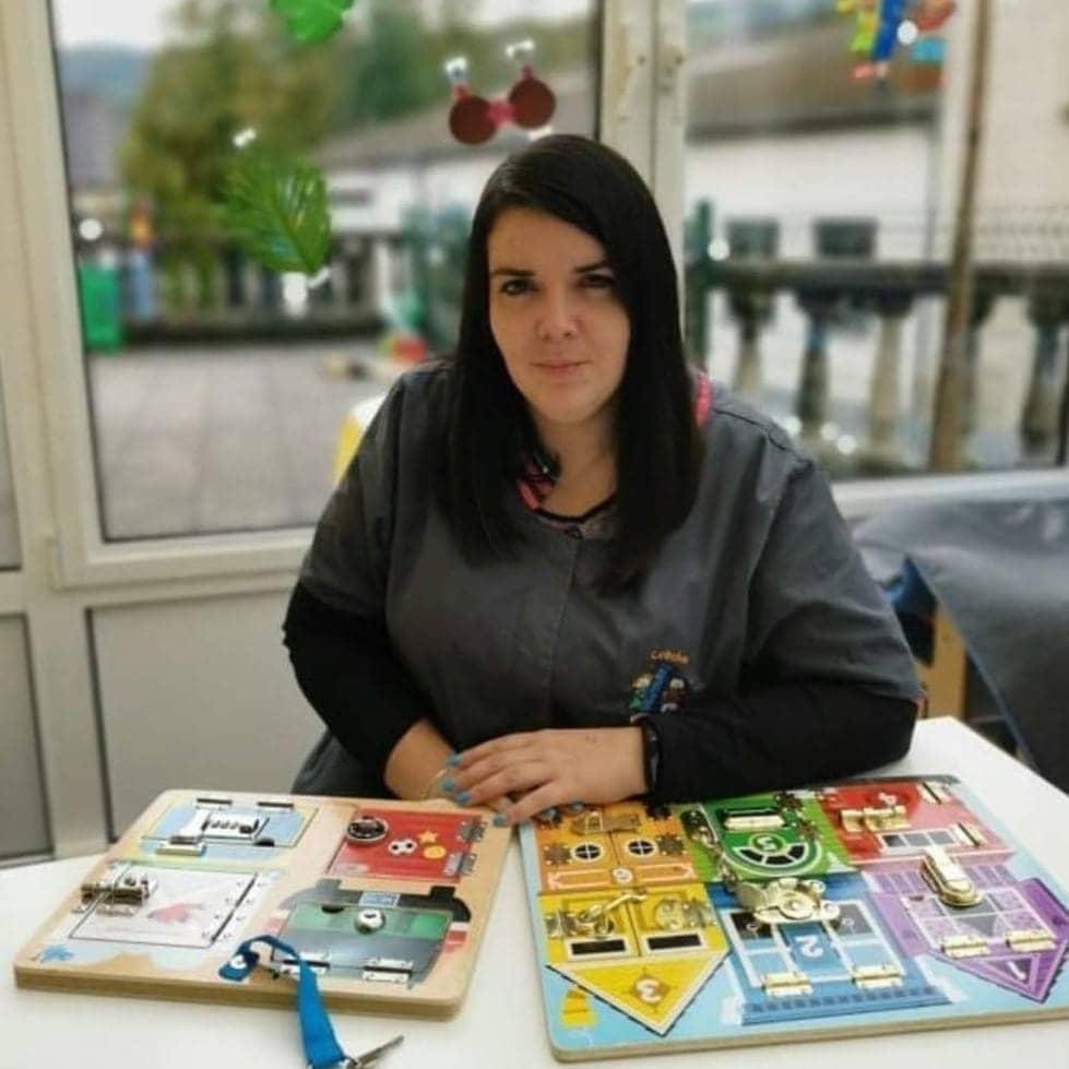 Femme aux cheveux noirs est assise devant une table où se trouvent des jeux pour enfants