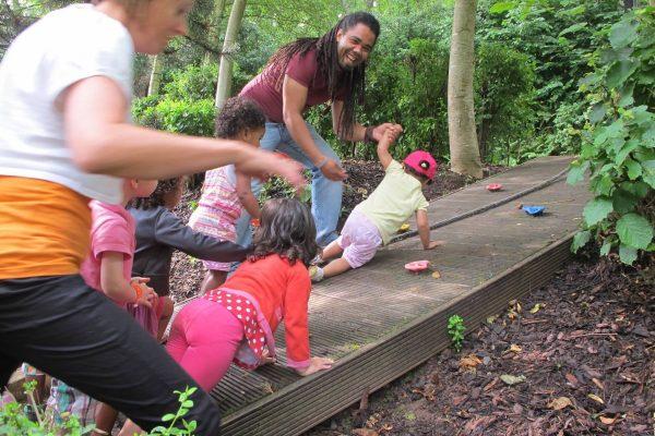 Cinq enfants accompagnés de deux éducateurs faisant de l'escalade dans les bois