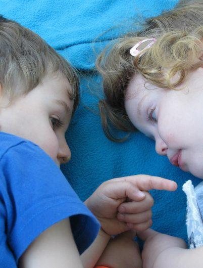 Deux enfants couchés sur une couverture bleue