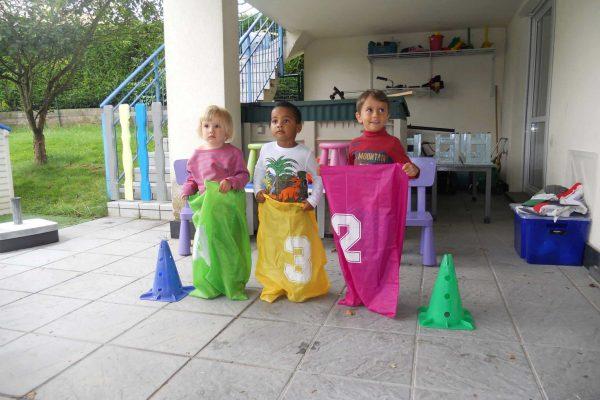 Trois enfants s'apprêtent à faire une course en sac