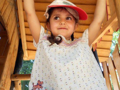 Une petite fille avec une casquette dans une plaine de jeux