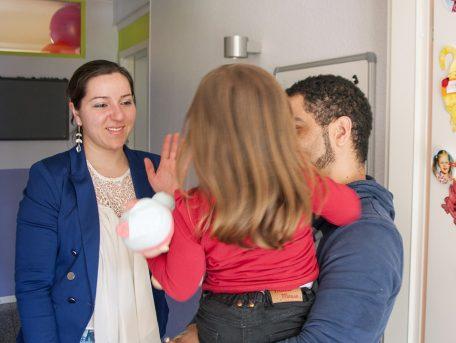 Une femme dans une crèche fait signe à sa fille qui est dans les bras d'un éducateur