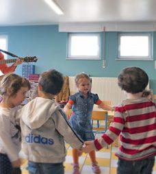 Enfants qui font une ronde avec un musicien qui joue de la guitare